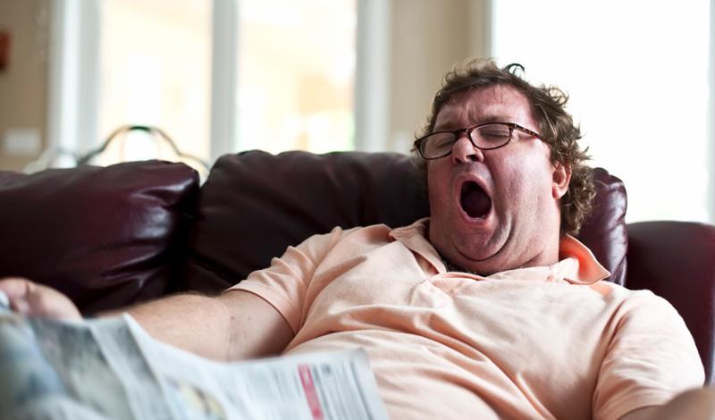 Полный мужчина зевает